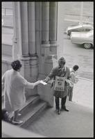 Activist hands a woman a flyer promoting April 4 as a Black holiday at a memorial service for Martin Luther King, Jr. at the Washington National Cathedral, 29 March 1969