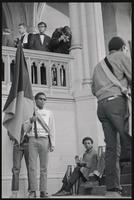 An activist holds a flag in front of musicians as a man photographs them from a balcony outside a memorial service for Martin Luther King, Jr. at the Washington National Cathedral, 29 March 1969