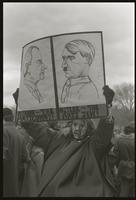 "An alternate view of a protester against Richard Nixon's second inauguration holding a sign comparing Nixon to Hitler (""Nixon -- the anti Commy! Hitler -- the anti Jew!""), 20 January 1973"
