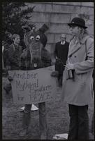 "An alternate view of a protester against Richard Nixon's second inauguration wearing an animal costume and holding a sign that reads ""Another Mythical Creature for PEACE,"" 20 January 1973"