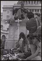 Alternate view of a Vietnam veteran adding his hat to the  pile of military decorations discarded at the base of the John Marshall statue on the US Capitol grounds during veteran demonstrations before Vietnam War Out Now, 23 April 1971