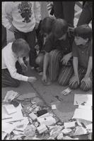 Alternate view of children picking up and examining military decorations discarded at the base of the John Marshall statue at the US Capitol during veteran demonstrations before Vietnam War Out Now, 23 April 1971