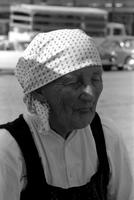 Alternate view of an elderly woman wearing a white head scarf