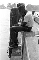 Adolescent male sitting on dock fishing