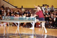 Action shot of Chinese athletes playing table tennis for a crowd of spectators
