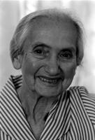 Alternate view of a smiling elderly woman wearing a striped dress