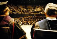 View of audience at commencement ceremony between faculty members on stage at American University, Washington, D.C.