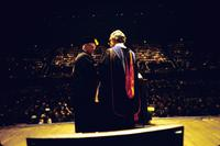 View of two men in academic robes with audience in background during awarding of honorary degrees at American University, Washington, D.C.