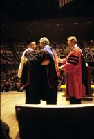 Two men embracing while on looks on during awarding of honorary degrees at American University, Washington, D.C.